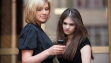 9071573-two-young-women-looking-at-mobile-phone